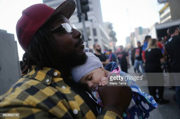 Dwayne Ray whose wife is Armenian holds their daughter Kiayah at a rally outside the Turkish Consulate during a march and rally commemorating the...