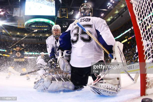 Dwayne Roloson and Steven Stamkos of the Tampa Bay Lightning react as the third period goal shot by Nathan Horton of the Boston Bruins enters the net...