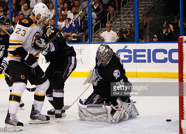 Dwayne Roloson Mike Lundin of the Tampa Bay Lightning and Chris Kelly of the Boston Bruins watch as a puck shot by Tyler Seguin of the Boston Bruins...