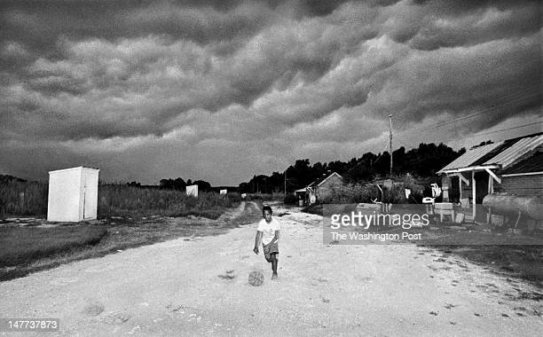 FILE Dwayne Sample heads toward shelter as a looming thunderstorm was just moments away in Bayview Virginia on December 23 1998 At left are some of...