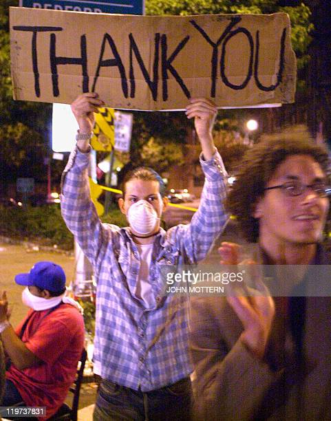 Dwayne Shirley holds up a sign as rescue workers and police come and go from the scene of the World Trade Center wreckage 13 September 2001 in New...