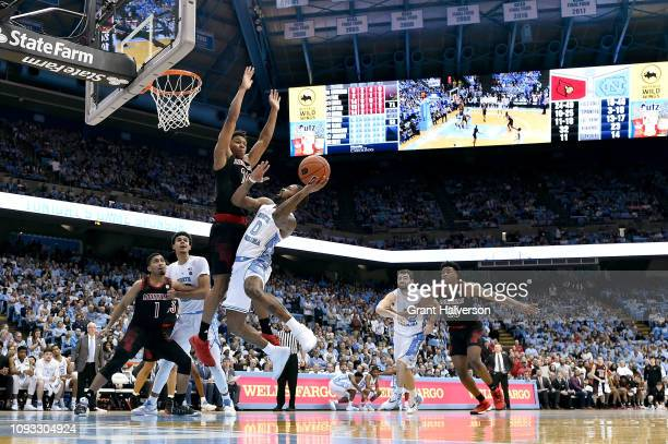 Dwayne Sutton of the Louisville Cardinals defends a shot by Seventh Woods of the North Carolina Tar Heels during the second half of their game at the...