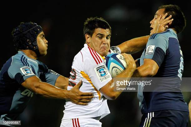 Dwayne Sweeney of the Chiefs fends the tackle of Chris Lowrey and Benson Stanley of the Blues during the Super Rugby trial match between the Chiefs...