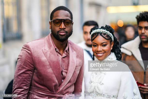 Dwayne Wade wears sunglasses, a pink velvet shirt, a pink velvet jacket, a matched belt ; Gabrielle Union wears a pearl headband, a white fluffy...