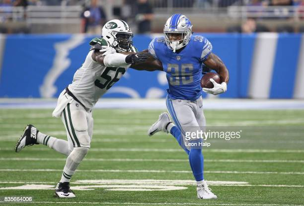 Dwayne Washington of the Detroit Lions runs for a first down as Demario Davis of the New York Jets makes the stop during the second quarter of the...