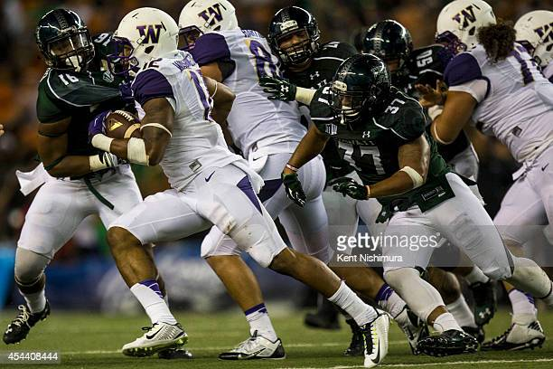 Dwayne Washington of the Washington Huskies carries the ball against the Hawaii Warriors during the second half of a college football game at Aloha...