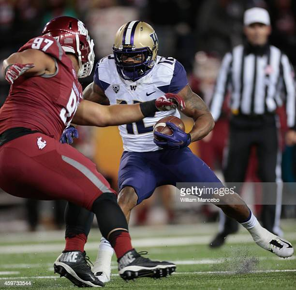 Dwayne Washington of the Washington Huskies carries the ball against Destiny Vaeao of the Washington State Cougars in the first half of the 107th...