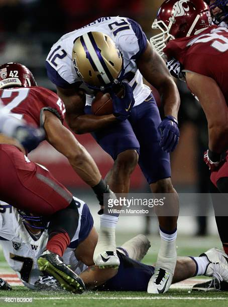 Dwayne Washington of the Washington Huskies carries the ball against the Washington State Cougars during the 107th Apple Cup at Martin Stadium on...