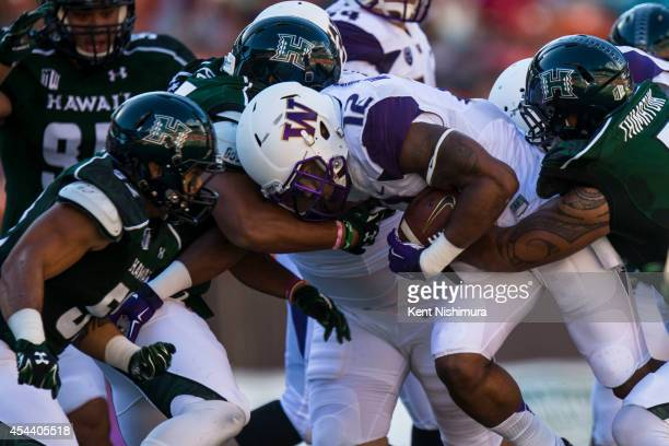 Dwayne Washington of the Washington Huskies is stopped by the Hawaii Warriors defense during the first quarter of a college football game between the...