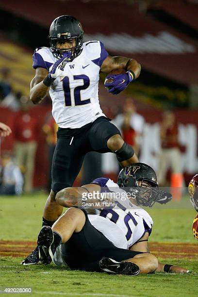 Dwayne Washington of the Washington Huskies leaps over Siosifa Tufunga of the Washington Huskies during the third quarter of a game against the USC...