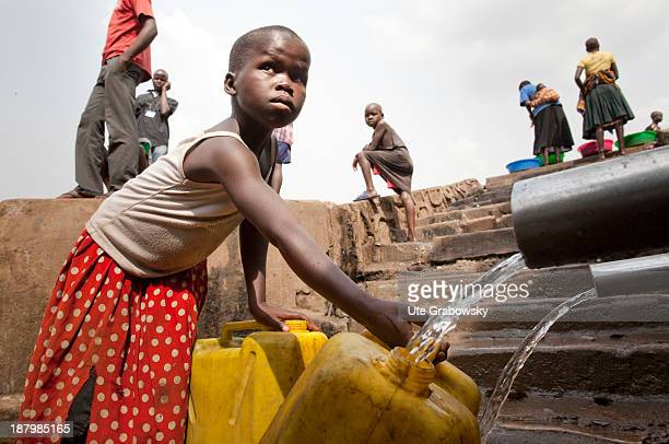 Dweller of the Kisenyi slum, child filling water cans at the watering hole.