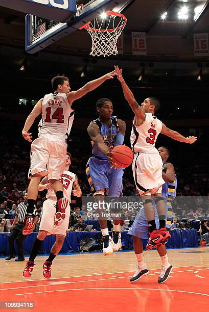 Dwight Buycks of the Marquette Golden Eagles passes the ball between Kyle Kuric and Peyton Siva of the Louisville Cardinals during the quarterfinals...