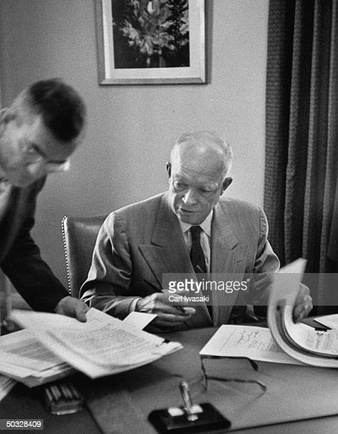 Dwight D Eisenhower signing papers with his assistant Wayne Hawks in his temporary office at Lowry Air Force Base