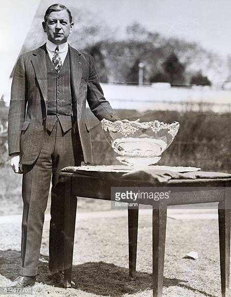 Dwight Davis stands beside the glass trophy cup awarded in the international lawn tennis tournament he founded, The Davis Cup.