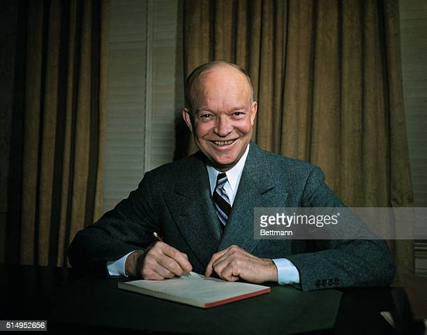 Dwight Eisenhower seated at desk with pen in hand
