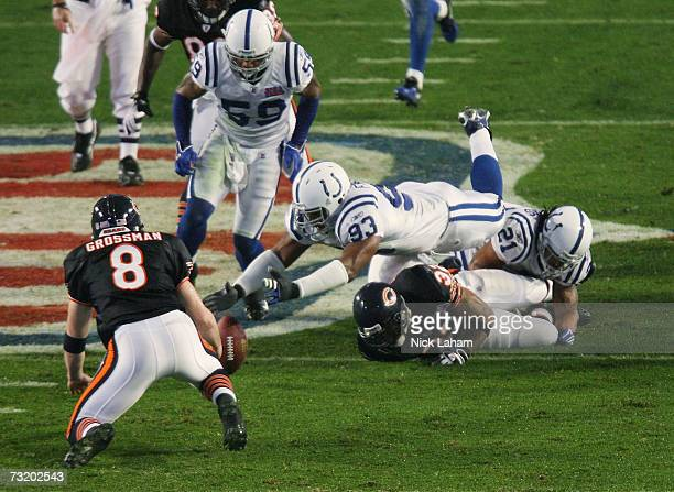 Dwight Freeney of the Indianapolis Colts stretches over running back Cedric Benson of the Chicago Bears and in front of quarter Rex Grossman to...
