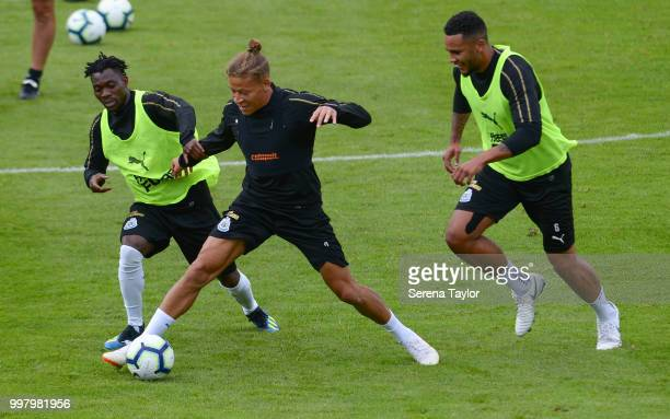 Dwight Gayle controls the ball whilst being challenged by Christian Atsu and Jamaal Lascelles during the Newcastle United Training session at Carton...