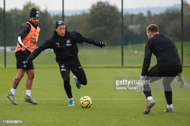 Dwight Gayle looks to strike the ball as he passes DeAndre Yedlin and into the line of Goalkeeper Rob Elliot during the Newcastle United Training...
