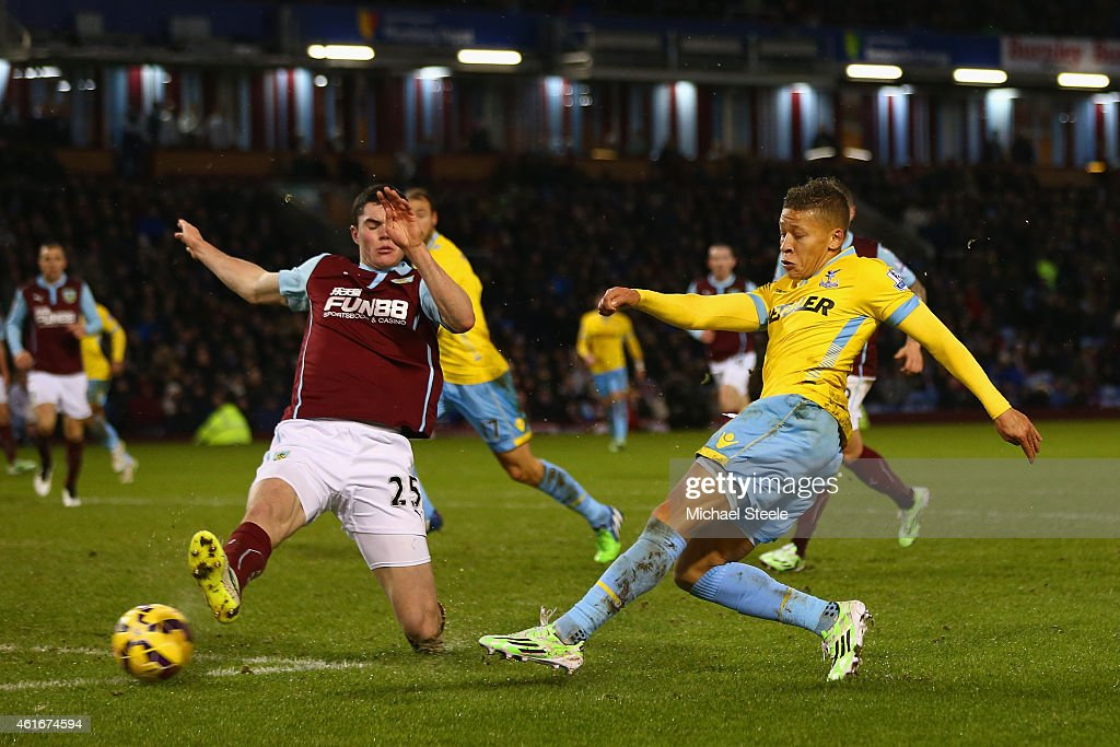 Dwight Gayle of Crystal Palace socres their third goal under pressure from Michael Keane of Burnley during the Barclays Premier League match between Burnley and Crystal Palace at Turf Moor on January 17, 2015 in Burnley, England.