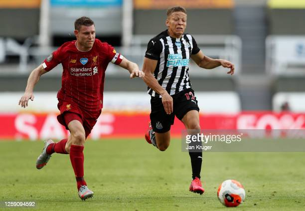 Dwight Gayle of Newcastle United and James Milner of Liverpool run for the ball during the Premier League match between Newcastle United and...