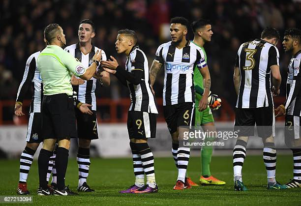 Dwight Gayle of Newcastle United argues with Referee Stephen Martin over the dismissal of Paul Dummett during the Sky Bet Championship match between...