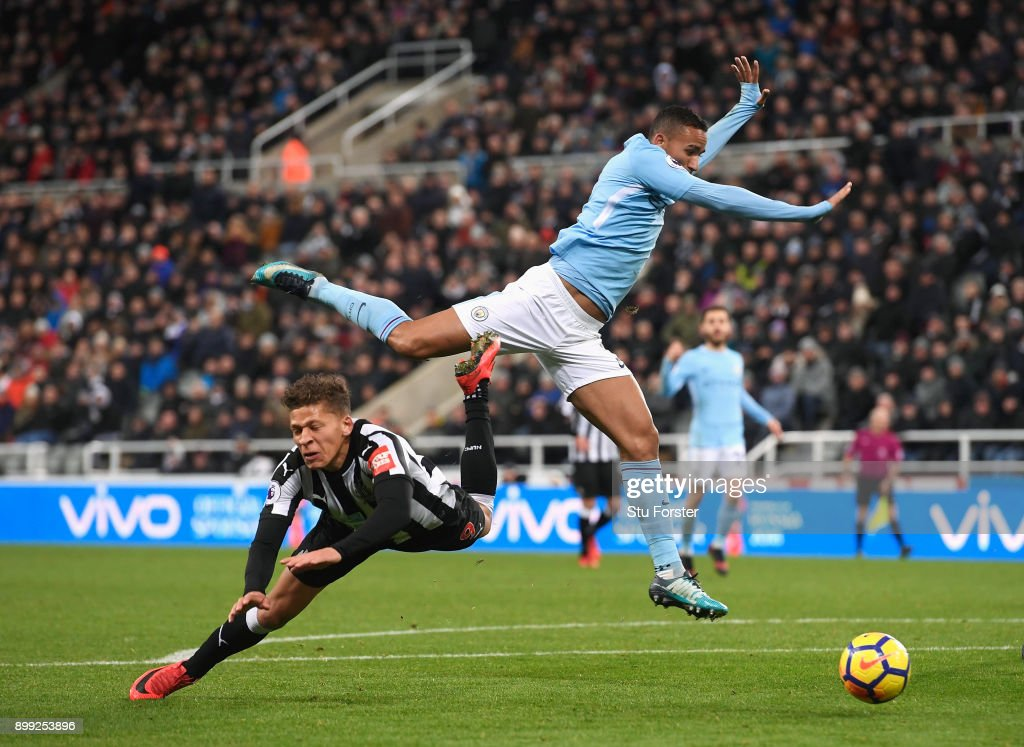 Dwight Gayle of Newcastle United goes to ground after a challenge with Danilo of Manchester City but is later booked for diving during the Premier League match between Newcastle United and Manchester City at St. James' Park on December 27, 2017 in Newcastle upon Tyne, England.