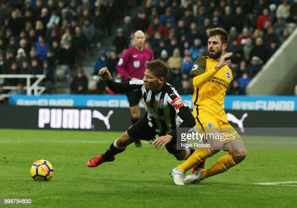 Dwight Gayle of Newcastle United goes to ground after a challenge from Davy Propper of Brighton and Hove Albion during the Premier League match...