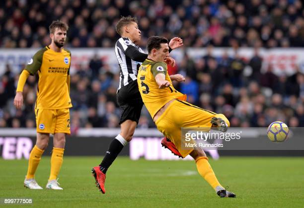 Dwight Gayle of Newcastle United is challenged by Lewis Dunk of Brighton and Hove Albion during the Premier League match between Newcastle United and...