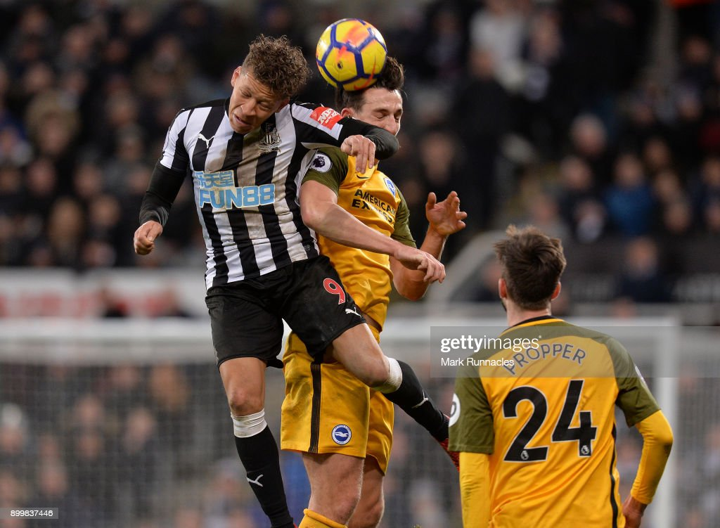 Dwight Gayle of Newcastle United is challenged by Lewis Dunk of Brighton during the Premier League match between Newcastle United and Brighton and Hove Albion at St. James Park on December 30, 2017 in Newcastle upon Tyne, England.