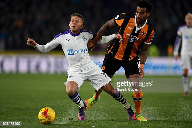 Dwight Gayle of Newcastle United is challenged by Tom Huddlestone of Hull City during the EFL Cup QuarterFinal match between Hull City and Newcastle...
