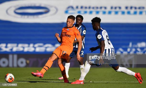 Dwight Gayle of Newcastle United passes the ball under pressure from Tariq Lamptey of Brighton and Hove Albion and Yves Bissouma of Brighton and Hove...