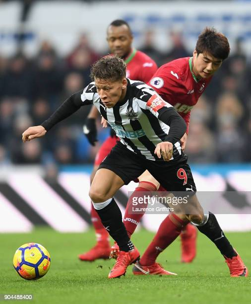 Dwight Gayle of Newcastle United runs with the ball away from the pressure of Ki SungYueng of Swansea City during the Premier League match between...