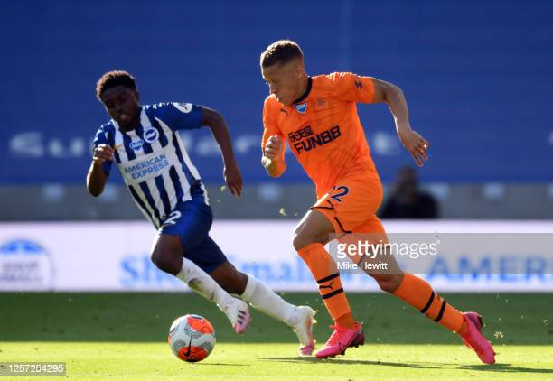 Dwight Gayle of Newcastle United runs with the ball under pressure from Tariq Lamptey of Brighton and Hove Albion during the Premier League match...