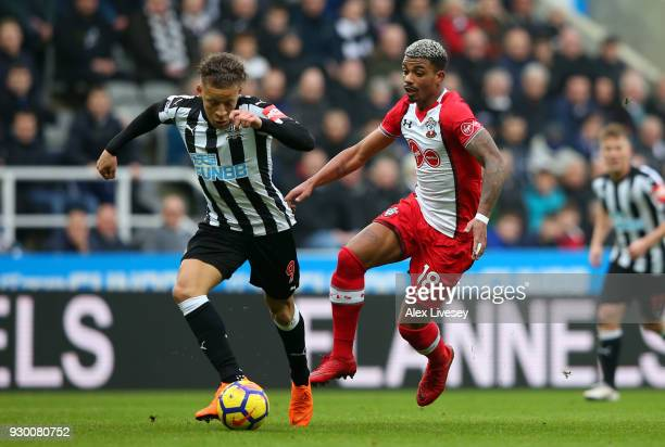 Dwight Gayle of Newcastle United runs with the ball under pressure from Mario Lemina of Southampton during the Premier League match between Newcastle...