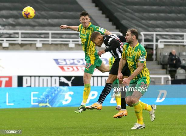 Dwight Gayle of Newcastle United scores their team's second goal under pressure from Dara O'Shea and Branislav Ivanovic of West Bromwich Albion...