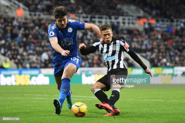 Dwight Gayle of Newcastle United shoots past Harry Maguire of Leicester City during the Premier League match between Newcastle United and Leicester...