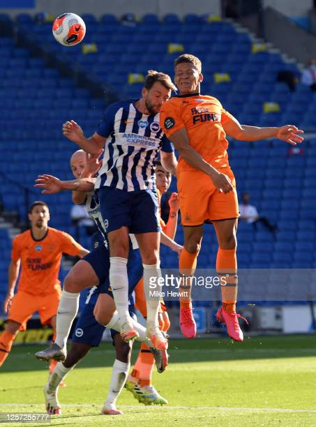 Dwight Gayle of Newcastle United wins a header under pressure from Dale Stephens of Brighton and Hove Albion during the Premier League match between...