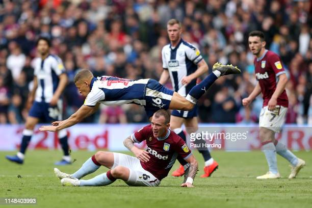 Dwight Gayle of West Bromwich Albion is challenged by Glenn Whelan of Aston Villa during the Sky Bet Championship Playoff semi final first leg match...