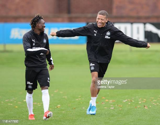 Dwight Gayle runs out to training holding his arms out with teammate Christian Atsu during the Newcastle United Training Session at the Newcastle...