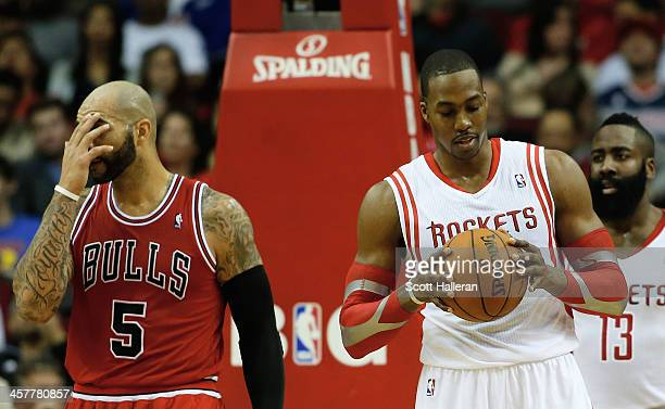 Dwight Howard and James Harden of the Houston Rockets wait under the basket alongside Carlos Boozer of the Chicago Bulls during the game at Toyota...