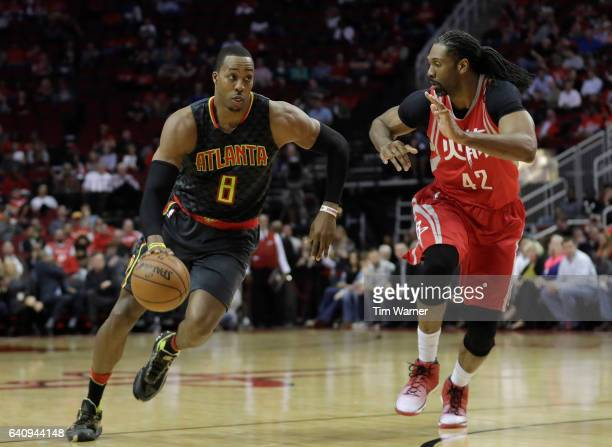 Dwight Howard of the Atlanta Hawks drives to the basket defended by Nene Hilario of the Houston Rockets in the first half at Toyota Center on...