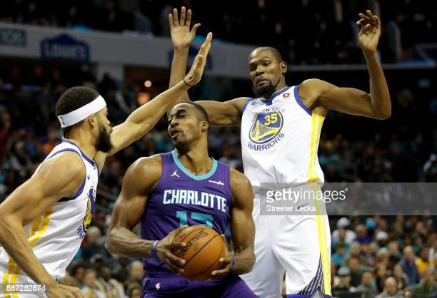 Dwight Howard of the Charlotte Hornets drives to the basket against teammates JaVale McGee and Kevin Durant of the Golden State Warriors during their...
