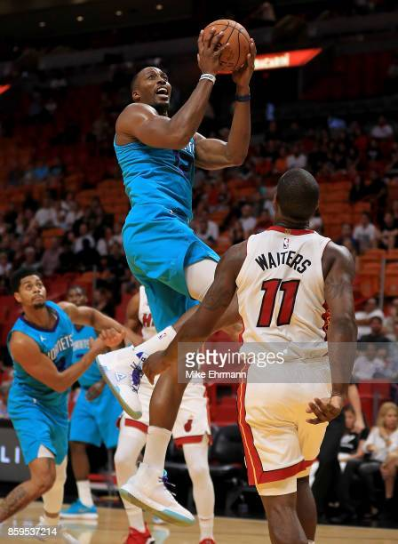 Dwight Howard of the Charlotte Hornets drives to the basket during a preseason game against the Miami Heat at American Airlines Arena on October 9...