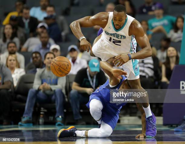 Dwight Howard of the Charlotte Hornets goes after a loose ball against Devin Harris of the Dallas Mavericks during their game at Spectrum Center on...