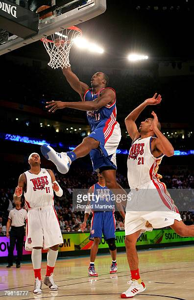 Dwight Howard of the Eastern Conference goes to the basket over Carmelo Anthony and Tim Duncan of the Western Conference during the 57th NBA AllStar...