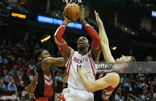 Dwight Howard of the Houston Rockets battles for the ball with Rudy Gay and Tyler Hansbrough of the Toronto Raptors at Toyota Center on November 11...