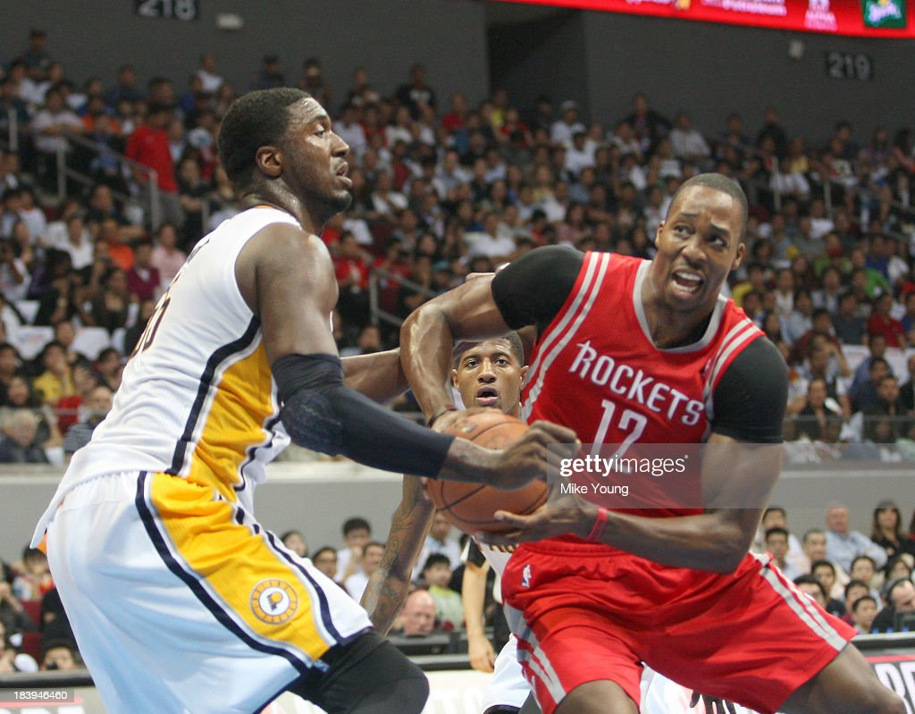 Dwight Howard #12 of the Houston Rockets drives against Roy Hibbert #55 of the Indiana Pacers during the NBA gane at the Mall of Asia Arena on October 10, 2013 in Manila, Philippines.