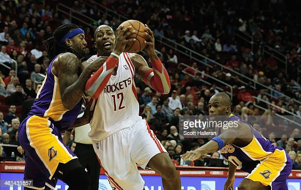 Dwight Howard of the Houston Rockets drives between Jordan Hill and Jodie Meeks of the Los Angeles Lakers during the game at the Toyota Center on...