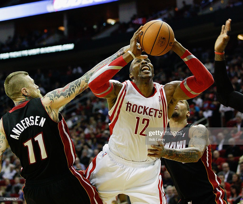 Dwight Howard #12 of the Houston Rockets drives to the basket between Chris Andersen #11 and Michael Beasley #8 of the Miami Heat at Toyota Center on March 4, 2014 in Houston, Texas.