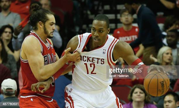 Dwight Howard of the Houston Rockets is grabbed unber the basket by Joakim Noah of the Chicago Bulls during the game at Toyota Center on December 18...